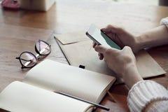 Vista del primo piano delle mani della donna con il telefono ed il blocco note, vetri, in caffè Fotografie Stock Libere da Diritti
