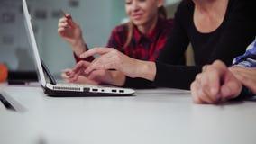 Vista del primo piano delle mani di un gruppo creativo di affari di tre genti che lavorano al computer portatile in un ufficio mo stock footage
