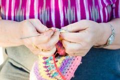 Vista del primo piano delle mani di una signora anziana che tricotta sui ferri da maglia, facendo uso della lana variopinta immagine stock libera da diritti