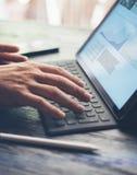 Vista del primo piano delle mani maschii che scrivono la stazione a macchina elettronica del tastiera-bacino della compressa Uomo Fotografia Stock Libera da Diritti