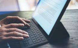 Vista del primo piano delle mani maschii che scrivono la stazione a macchina elettronica del tastiera-bacino della compressa Uomo Fotografia Stock