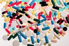 Vista del primo piano delle pillole mediche variopinte e della siringa Immagini Stock Libere da Diritti