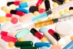 Vista del primo piano delle pillole mediche variopinte e delle siringhe Fotografia Stock Libera da Diritti