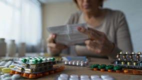 Vista del primo piano delle pillole sulla tavola e sulla donna anziana che prendono medicina dietro, consumismo archivi video