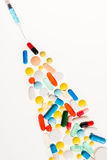 Vista del primo piano delle pillole variopinte e della siringa su bianco Fotografia Stock Libera da Diritti
