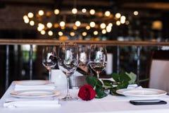 Vista del primo piano di bello fiore della rosa rossa con vino alla tavola immagine stock libera da diritti
