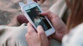 Vista del primo piano di giovani coppie che si siedono sulla spiaggia, sulla sabbia e guardanti le foto sullo smartphone, facendo video d archivio