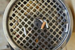 Vista del primo piano di grande portacenere con le sigarette cadute Fotografie Stock Libere da Diritti