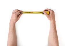 Vista del primo piano di man& x27; la s passa la misurazione del qualcosa con la nastro-misura isolata su fondo bianco fotografie stock