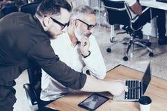 Vista del primo piano di nuovo progetto di affari di presentazione Il giovane barbuto passa indicare il computer portatile modern Fotografie Stock