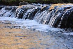Vista del primo piano di poca cascata sul fiume fotografia stock