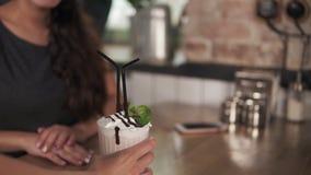 Vista del primo piano di un cocktail portato dal cameriere per le giovani coppie che si siedono alla tavola di legno in caffetter video d archivio