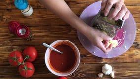 Vista del primo piano del formaggio grattare della donna su pizza sulla cucina archivi video