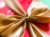 Vista del primo piano del nastro o dell'arco dell'oro sul contenitore di regalo rosso immagini stock libere da diritti