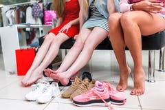 Vista del primo piano a piedi nudi lungamente delle gambe femminili esili circondate da varietà di scarpe di sport Una seduta fem Immagine Stock