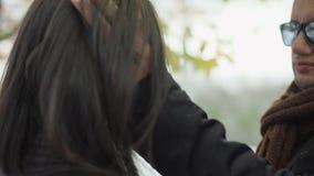 Vista del primo piano sopra la spalla della donna sul bello uomo latino nel movimento lento nevoso della foresta video d archivio