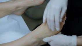 Vista del primo piano sulle mani della massaggiatrice che fanno rubdown del piede alla donna video d archivio