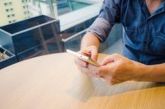 Vista del primo piano del telefono cellulare nelle mani di un uomo, mani dello smartphone di tenuta maschio mentre sedendosi in u fotografia stock