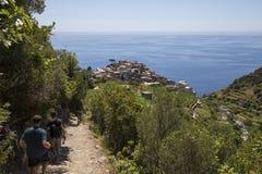 Vista del pueblo de Corniglia de la trayectoria en la colina y dos viajeros Foto de archivo