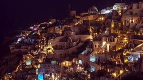 Vista del pueblo de Oia, Santorini, Grecia, en la noche con la gente que acomete alrededor, timelapse, inclinación, cacerola, enf almacen de video