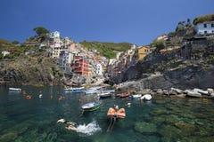 Vista del pueblo de Riomaggiore y de la natación joven de los pares Foto de archivo libre de regalías