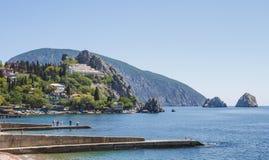 Vista del pueblo, situada en la orilla rocosa del Mar Negro, y los rompeolas en el primero plano fotografía de archivo libre de regalías