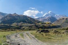 Vista del pueblo Stepantsminda, de la iglesia de la trinidad y del soporte Kazbek de Gergeti en tiempo soleado Fotografía de archivo libre de regalías
