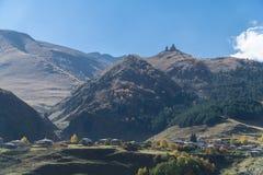 Vista del pueblo Stepantsminda y de la iglesia de la trinidad de Gergeti en tiempo soleado Foto de archivo libre de regalías