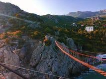 Vista del puente de cuerda roja de la suspensión en fondo de la montaña foto de archivo libre de regalías