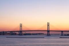 Puente de la bahía sobre salida del sol en Yokohama, Japón imagenes de archivo
