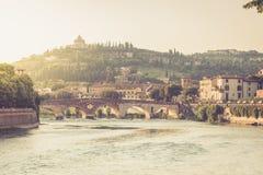 Vista del puente de Ponte Pietra en el r?o del Adigio iluminado por la puesta del sol en Verona foto de archivo