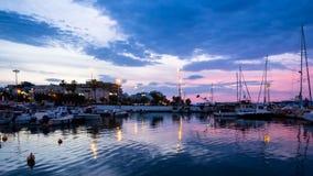 Vista del puerto de Corinto con los barcos y los embarcaderos tirados en la oscuridad azul y rosada fotos de archivo