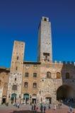 Vista del quadrato con la gente, la vecchia costruzione e la torre a San Gimignano Fotografia Stock