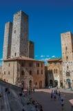 Vista del quadrato con la gente, la vecchia costruzione e la torre a San Gimignano Immagini Stock