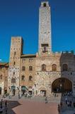 Vista del quadrato con la gente, la vecchia costruzione e la torre a San Gimignano Fotografia Stock Libera da Diritti