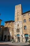 Vista del quadrato con la gente, la vecchia costruzione e la torre a San Gimignano Immagini Stock Libere da Diritti