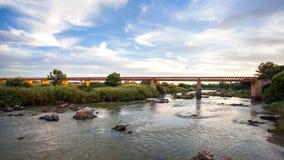 Vista del río anaranjado con el puente en Suráfrica Foto de archivo
