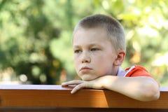 Vista del ragazzo ad un banco fotografia stock