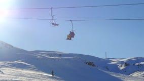 Vista del remonte de mudanza con snowboard de la gente y de los sportsmens de la montaña nevosa en fondo almacen de video