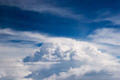 Vista del sedile di finestra dell'aeroplano di grandi nuvole lanuginose spesse bianche con un chiaro cielo blu Fotografia Stock