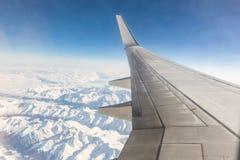 Vista del sedile di finestra dell'aeroplano mentre sorvolando le montagne nevose Immagini Stock Libere da Diritti