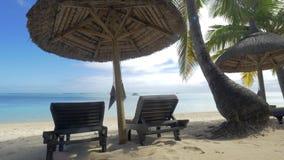 Vista del sillón vacío cerca del paraguas y de las palmeras nativos de sol contra el agua azul, Mauritius Island almacen de metraje de vídeo