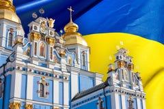 Vista del St Michaels Golden-Domed Monastery en Kiev, la iglesia ortodoxa ucraniana - patriarcado de Kiev, en la bandera del fond foto de archivo