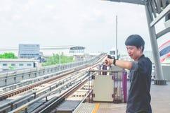 Vista del supporto asiatico dell'uomo ed esaminare il suo orologio mentre aspettando qualcosa o preoccupandosi per il tempo Treno fotografia stock