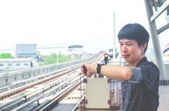 Vista del supporto asiatico dell'uomo ed esaminare il suo orologio mentre aspettando qualcosa o preoccupandosi per il tempo Treno immagini stock libere da diritti