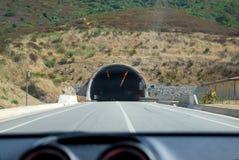 Vista del túnel del camino y de la montaña dentro del coche en día soleado Fotografía de archivo