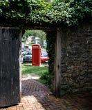 Vista del telefono rosso antico tramite il portone aperto Fotografie Stock Libere da Diritti