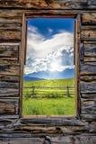 Vista del Tetons attraverso una finestra di cabina Fotografia Stock Libera da Diritti