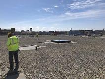 Vista del tetto; Roofers che ispezionano piattaforma; riparazioni di tetto sul tetto equilibrato dell'annuncio pubblicitario di E Immagine Stock Libera da Diritti