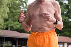 Vista del torso di chested nudo dell'uomo più anziano nell'usura gialla del costume da bagno immagine stock
